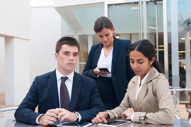 Pessoas de negócios sérios usando gadgets na mesa ao ar livre