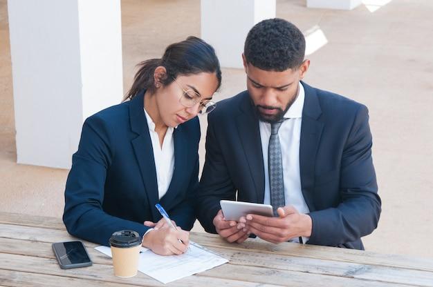 Pessoas de negócios sérios usando tablet e trabalhando na mesa