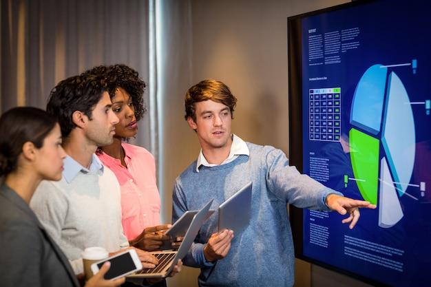 Pessoas de negócios, tendo a discussão sobre um gráfico na sala de conferências