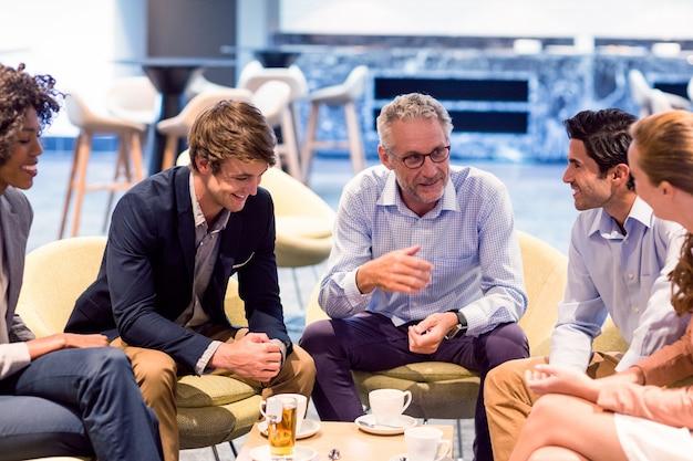 Pessoas de negócios, tendo uma discussão na cantina