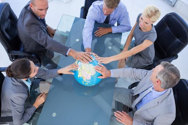 Pessoas de negócios tocando um globo