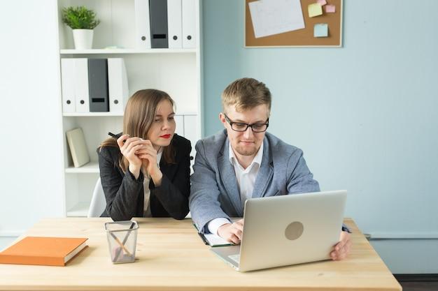 Pessoas de negócios, trabalho em equipe e conceito de escritório - mulher e homem estão trabalhando juntos no projeto de inicialização no escritório.