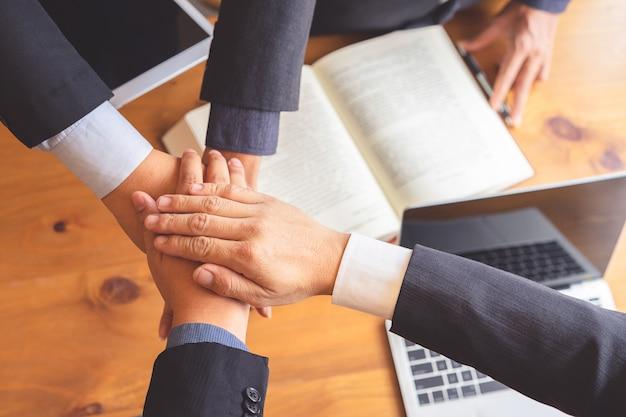 Pessoas de negócios, unir as mãos após reunião bem sucedida.