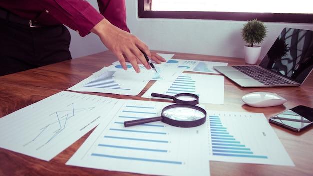 Pessoas de negócios usam caneta para apontar gráficos para analisar dados e estatísticas da empresa