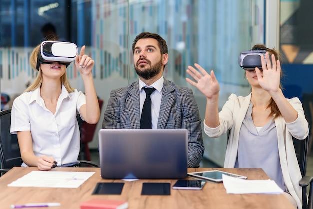 Pessoas de negócios usando óculos de realidade virtual durante a reunião. equipe de desenvolvedores testando o fone de ouvido de realidade virtual e discutindo novas idéias para melhorar a experiência visual.