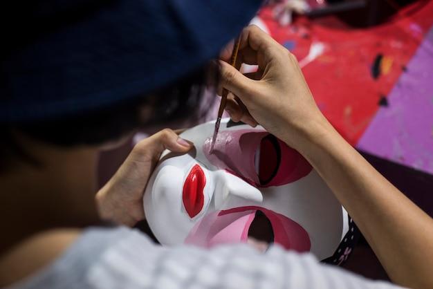 Pessoas de pintura a mão estão pintando a máscara da china