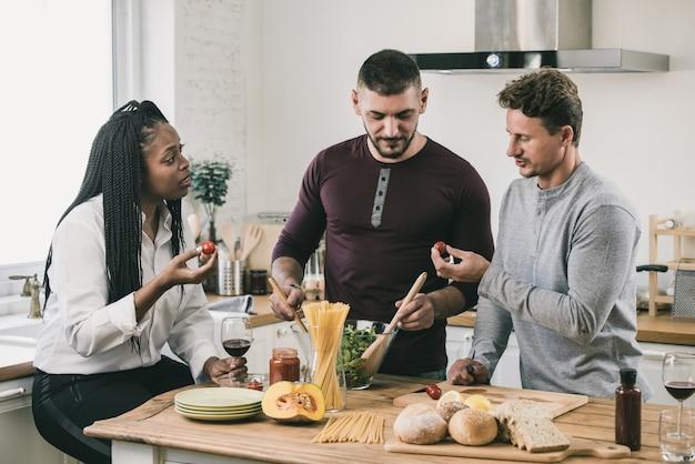 Pessoas de raça mista, cozinhando na cozinha