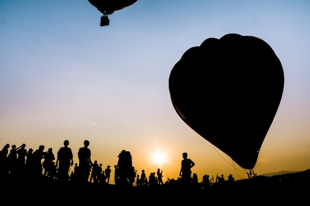 Pessoas de silhueta no festival de balão no lindo céu do sol no parque de singha