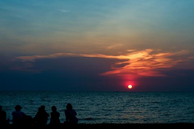 Pessoas de silhueta olham o céu pôr do sol na praia