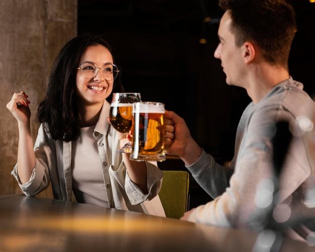 Pessoas de tiro médio com canecas de cerveja
