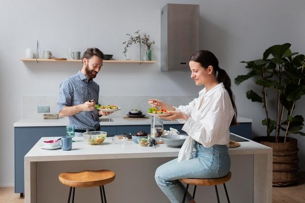 Pessoas de tiro médio comendo salada