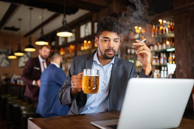 Pessoas, dependência de álcool de nicotina e conceito de maus hábitos. close de um homem bebendo cerveja, fumando um cigarro no bar