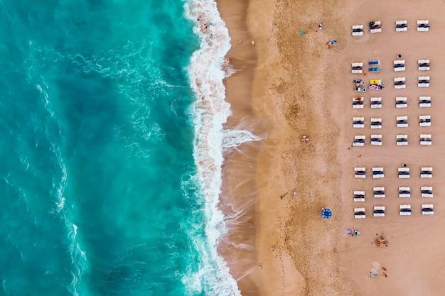 Pessoas descansando na praia aproveitam as férias de verão