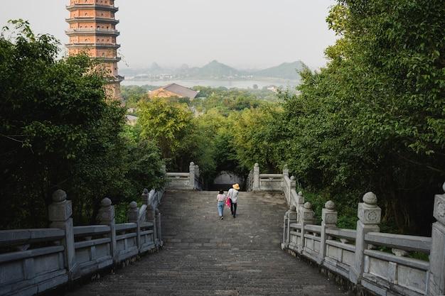 Pessoas descendo as escadas entre as árvores no templo bai dinh