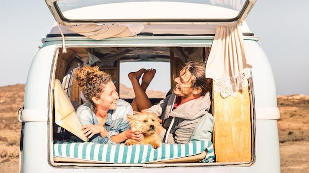 Pessoas descoladas com um cachorro fofo viajando juntos em uma minivan vintage