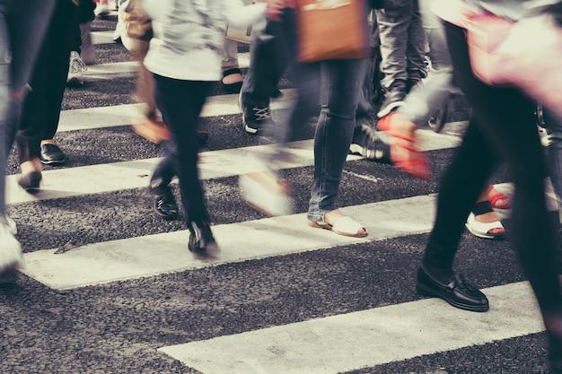 Pessoas desfocadas cruzando a rua em uma passadeira