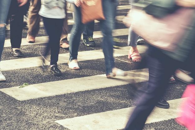 Pessoas desfocadas irreconhecíveis andando pela cidade.