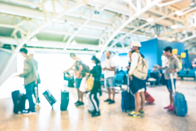 Pessoas desfocadas turva, esperando na fila no portão terminal do aeroporto internacional para viagem de avião