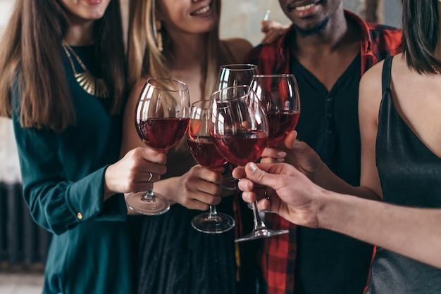 Pessoas desfrutando de bebidas no café. amigos no bar brindando vinho e sorrindo