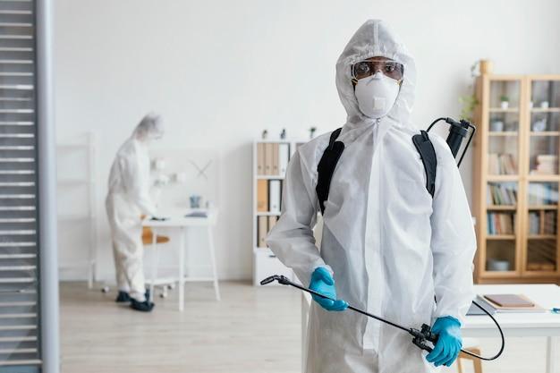 Pessoas desinfetando juntas uma área perigosa
