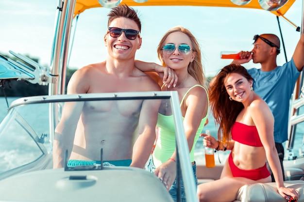 Pessoas despreocupadas. empresa de jovens satisfeitos aproveitando seu fim de semana enquanto dirigem um cruzeiro de férias no verão