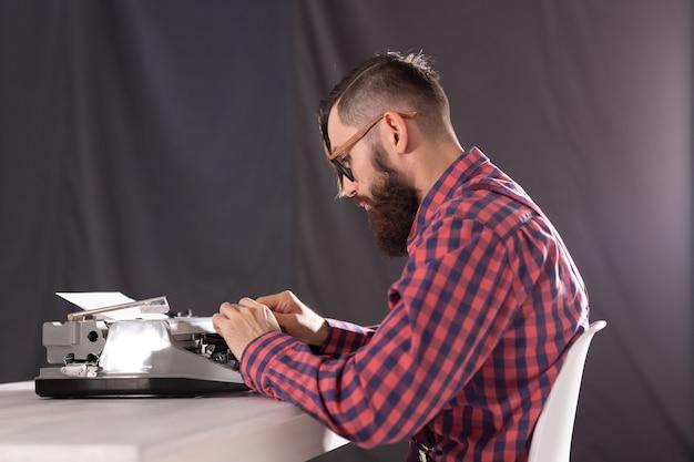 Pessoas, dia mundial do conceito de escritor e hipster - jovem jornalista elegante trabalhando na máquina de escrever.