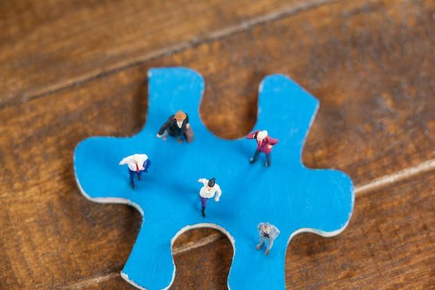Pessoas diminutos em um quebra-cabeça