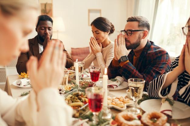 Pessoas dizendo graça na mesa de jantar