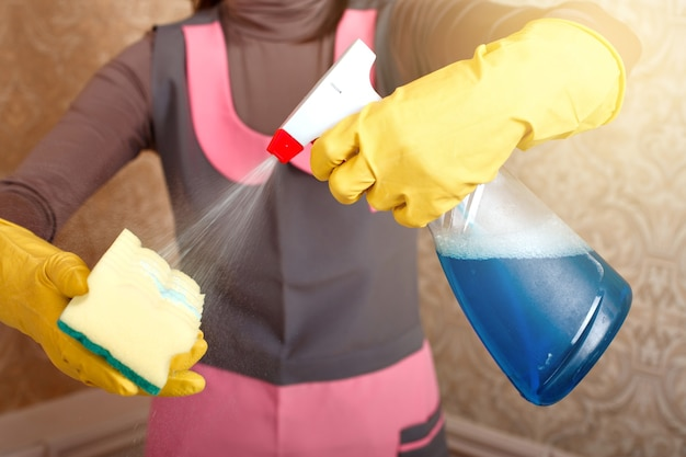Pessoas do sexo feminino com as mãos em luvas de borracha funcionam com esponja de lavagem e agente de limpeza. conceito de limpeza