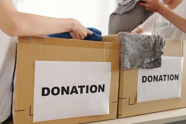 Pessoas doando roupas em centro de caridade, estão colocando calças e camisetas em caixas de papelão