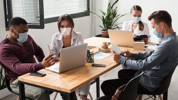 Pessoas durante a pandemia trabalhando juntas no escritório com máscaras