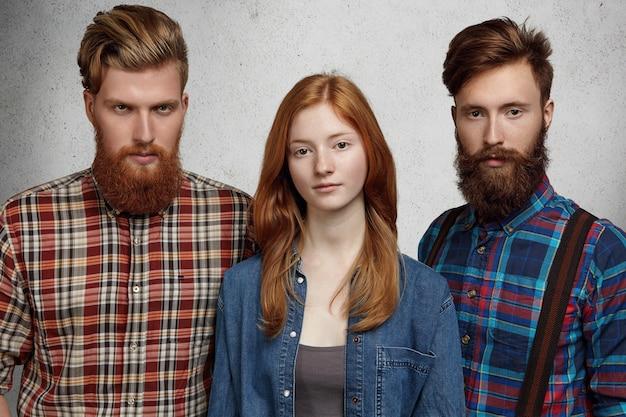 Pessoas e amizade. grupo de três alunos em roupas casuais, posando dentro de casa.