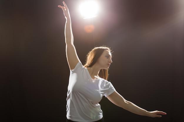 Pessoas e conceito de dança - jovem bela mulher desportiva dançando jazz funk em um fundo preto do estúdio.