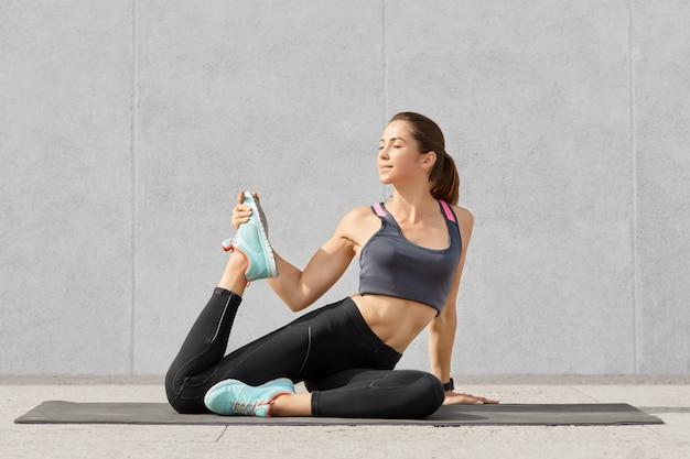 Pessoas e conceito de exercícios ativos. bela jovem europeia com cabelos escuros, vestida com roupas esportivas