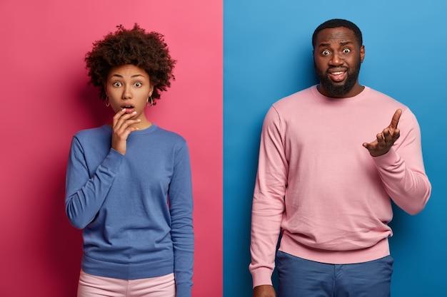 Pessoas e emoções. garota afro-americana perplexa e maravilhada, homem com barba descontente levanta a palma da mão