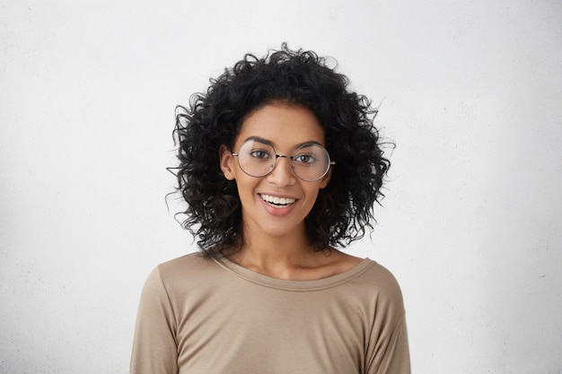 Pessoas e estilo de vida. emoções e sentimentos. mulher bonita positiva estudante de pele escura em roupas casuais e óculos redondos elegantes sorrindo alegremente, sentindo-se animado com o primeiro dia na universidade