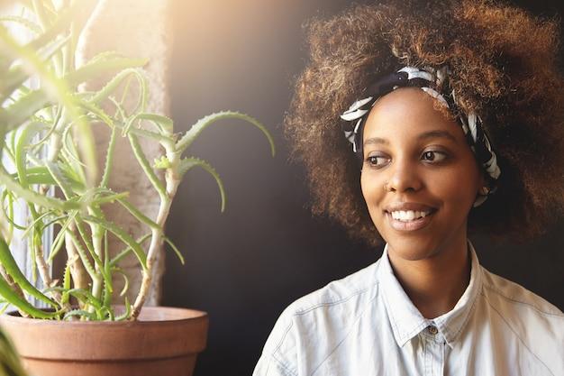 Pessoas e lazer. encantadora jovem africana vestindo pano e piercing facial, descansando dentro de casa, olhando pela janela com um lindo sorriso pensativo.