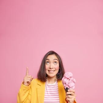 Pessoas e o conceito de junk food. mulher asiática satisfeita com cabelo escuro focado acima indica um espaço em branco para o seu anúncio segurando um sorvete delicioso e usa roupas estilosas isoladas na parede rosa