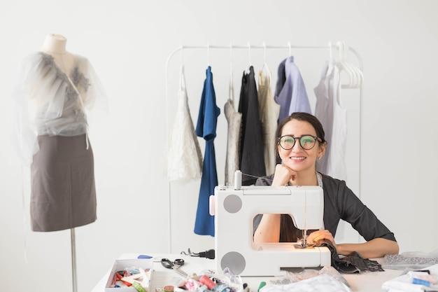 Pessoas e o conceito de moda - mulher jovem costureira costura roupas na máquina de costura.