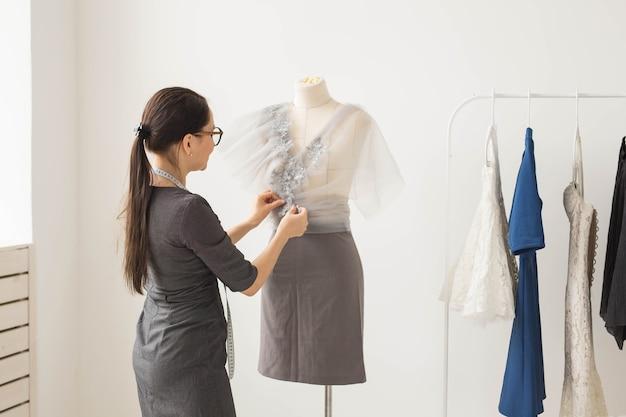 Pessoas e o conceito de moda - vista traseira do dono da loja de moda vestido com materiais de medição de roupa elegante no manequim no escritório.