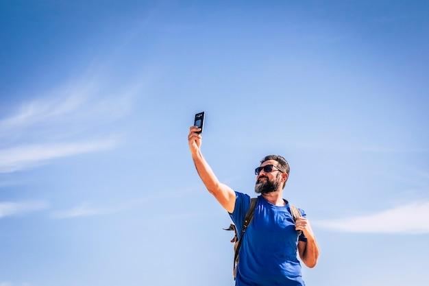 Pessoas e tecnologia da internet homem com barba e óculos de sol à procura de sinal com um dispositivo de telefone celular pessoas viajando com mochila para o conceito de aventura e férias alternativas no céu azul