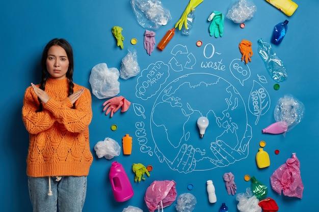 Pessoas, ecologia, proibição, conceito de recusa. garota asiática séria mantém os braços cruzados sobre o peito, diz não ao plástico, sendo ecologicamente correta, encosta na parede azul