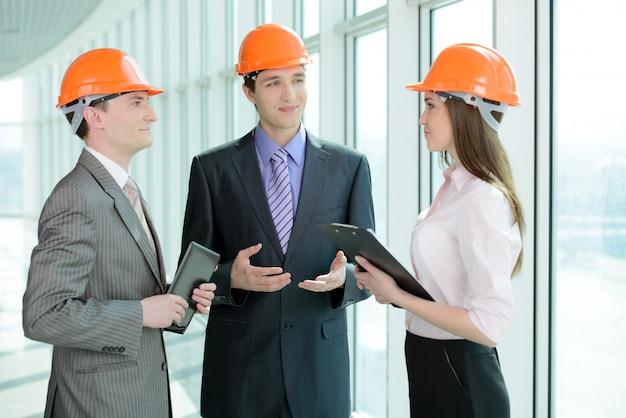 Pessoas em capacetes em um canteiro de obras.
