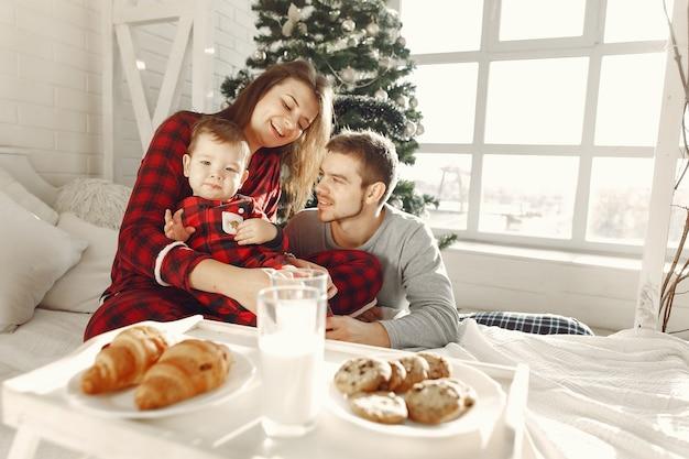 Pessoas em casa. família de pijama. leite e croissants em uma bandeja.