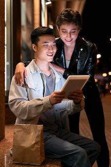 Pessoas em filmagem média olhando para um tablet