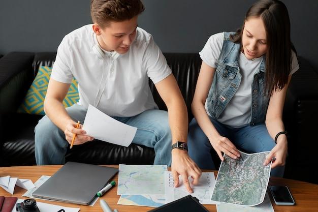 Pessoas em filmagem média planejando uma viagem em casa