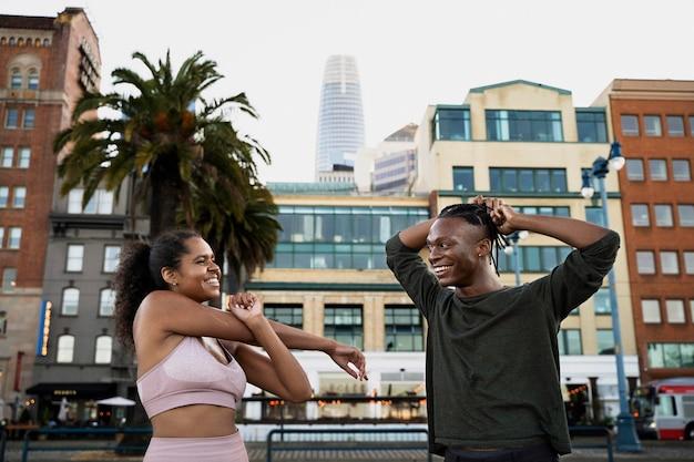 Pessoas em filmagem média se alongando ao ar livre
