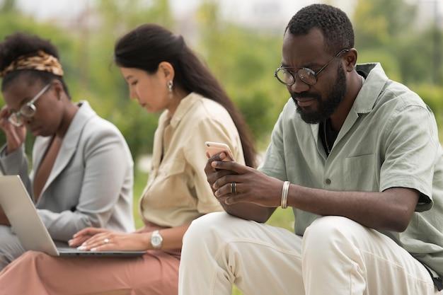 Pessoas em filmagem média sentadas ao ar livre