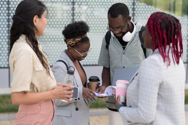 Pessoas em filmagens médias conversando ao ar livre