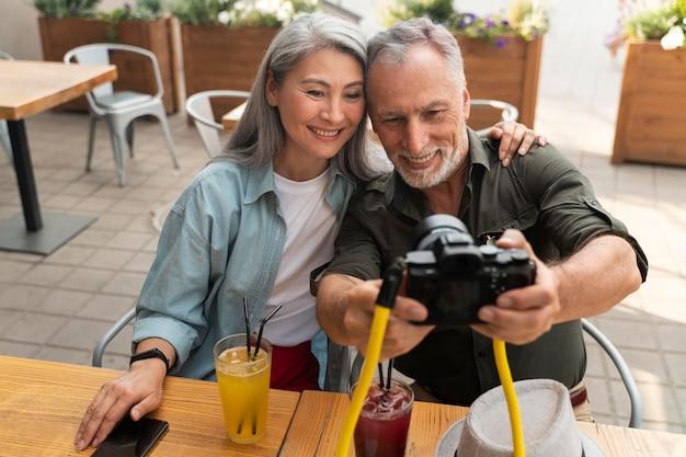 Pessoas em filmagens médias tirando selfie com a câmera